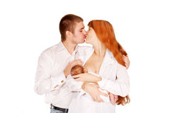 Parents kissing, baby breast-feeding Royalty Free Stock Photo