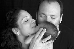 Parents kissing baby. Parents closeup both giving an affectionate kiss to a tiny baby in monochrome on a dark background Stock Images