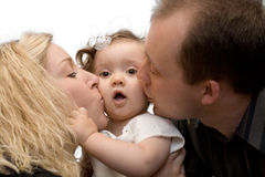 Parents kissing baby girl, isolated Stock Photos