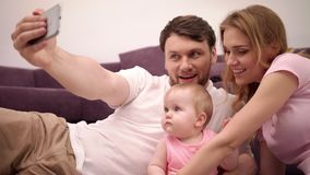 Parents kissing baby. Happy family taking selfie photo at home stock video