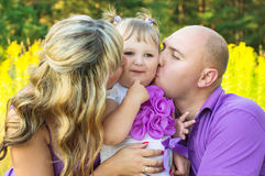Parents kissing baby Royalty Free Stock Photos