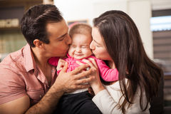 Parents kissing baby at the same time Royalty Free Stock Images