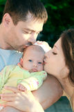 Parents kissing beautiful baby girl Stock Photo