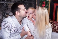 Parents kissing cute funny child stock photography