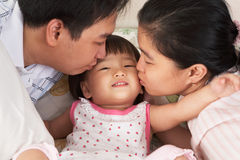 Parents kissing daughter Stock Images