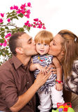 Parents kissing daughter Stock Photo