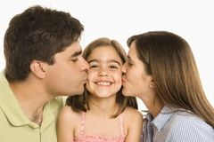 Parents kissing daughter. Mother and father kissing smiling daughter on cheek Stock Image
