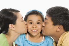 Parents kissing daughter. Asian mother and father kissing opposite cheeks of smiling daughter in front of white background Royalty Free Stock Photos