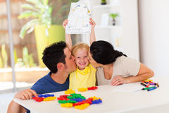 Parents kissing daughter. Happy parents kissing cute little daughter with her drawing Stock Photo