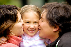 Parents kissing daughter Royalty Free Stock Image