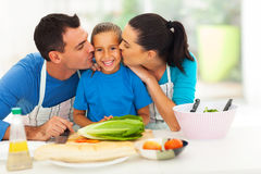 Parents kissing daughter. Loving parents kissing little daughter in kitchen Royalty Free Stock Photos