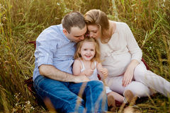 Parents kissing daughter on the nature, happy family, smile Stock Photography