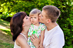 Parents kissing daughter Stock Photography