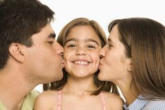 Parents kissing girl. Royalty Free Stock Photos