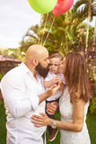 Parents kissing grumpy. Latino parents kissing grumpy son in sun light Royalty Free Stock Photo