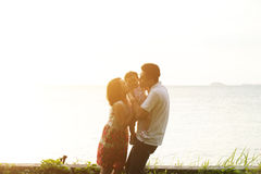 Parents kissing kid on beach sunset Royalty Free Stock Photos