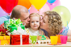 Parents kissing kid girl on birthday party Royalty Free Stock Image