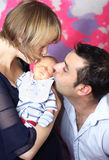 Parents kissing newborn baby. Portrait of a first time parents kissing the new baby Stock Photo
