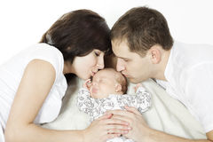 Parents kissing newborn baby Stock Photography