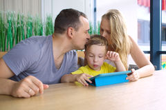 Parents kissing son playing on pad Royalty Free Stock Photography