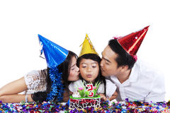 Parents kissing their child in birthday party Stock Image