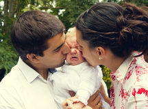 Parents kissing their crying baby Royalty Free Stock Photos