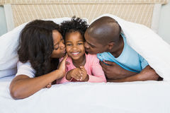 Parents kissing their daughter Royalty Free Stock Photos