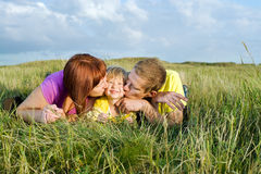 Parents kissing their daughter lying on a green meadow Royalty Free Stock Image