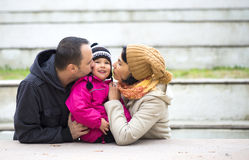 Parents kissing their girl Royalty Free Stock Images