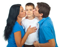 Parents kissing their son. Boy standing in the middle of his parents and being kissed isolated on white background Royalty Free Stock Photography