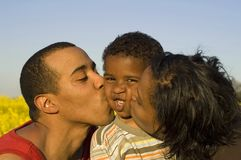 Parents kissing their son. Big kiss, funny expression, lots of love Royalty Free Stock Image