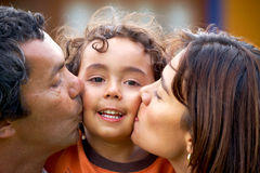 Parents kissing their son Stock Image
