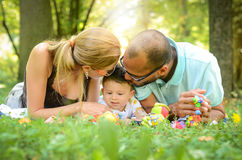 Parents are kissing their son. Happy interracial family is enjoying a day in the park Royalty Free Stock Images