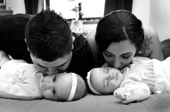 Parents kissing their twins. Parents kissing thei twins children Royalty Free Stock Photography