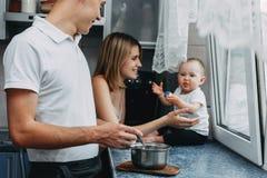 Parents la cocina de alimentación de la hija del bebé en casa fotografía de archivo
