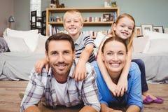 Parents la mentira en piso mientras que los niños que se sientan en su parte posterior foto de archivo libre de regalías