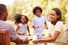 Parents la relajación mientras que juego de niños en jardín foto de archivo libre de regalías