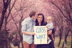 Parents la tenuta del loro bambino con la congettura che cosa? segno fotografie stock libere da diritti