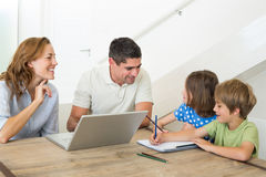 Parents with laptop assisting children coloring Royalty Free Stock Image