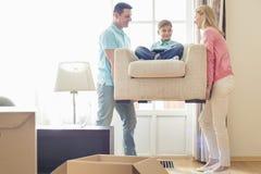 Parents le fils de transport sur le fauteuil dans la nouvelle maison Image libre de droits