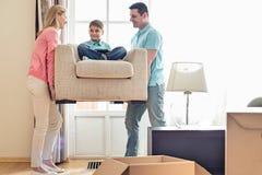 Parents le fils de transport sur le fauteuil dans la nouvelle maison Photographie stock libre de droits