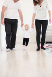 Parents learning their beautiful baby girl how to walk. Royalty Free Stock Photography
