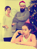 Parents lecturing daughter at Christmas. Young father and mother correcting their child for disobedience at Christmas Stock Photography