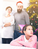 Parents lecturing daughter at Christmas. Young parents lecturing their daughter for bad behavior at Christmas Stock Photo