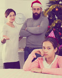 Parents lecturing daughter at Christmas. Young parents lecturing their daughter for bad behavior at Christmas Royalty Free Stock Photography