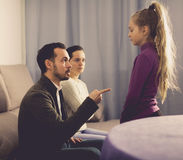 Parents lecturing daughter. Young father and mother correcting their child for disobedience Stock Photos