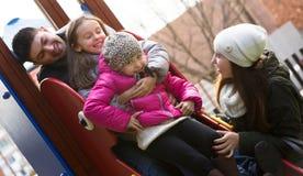 Parents les enfants de aide sur la glissière Photos libres de droits