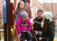 Parents les enfants de aide sur la glissière Image stock