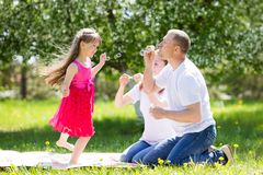 Little girl is playing with soap bubbles. stock photo