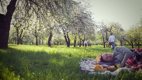 Parents lie on the grass in the park, and two daughters running around. Mother lies on the grass. Dad and two daughters running and playing on the background of stock video footage